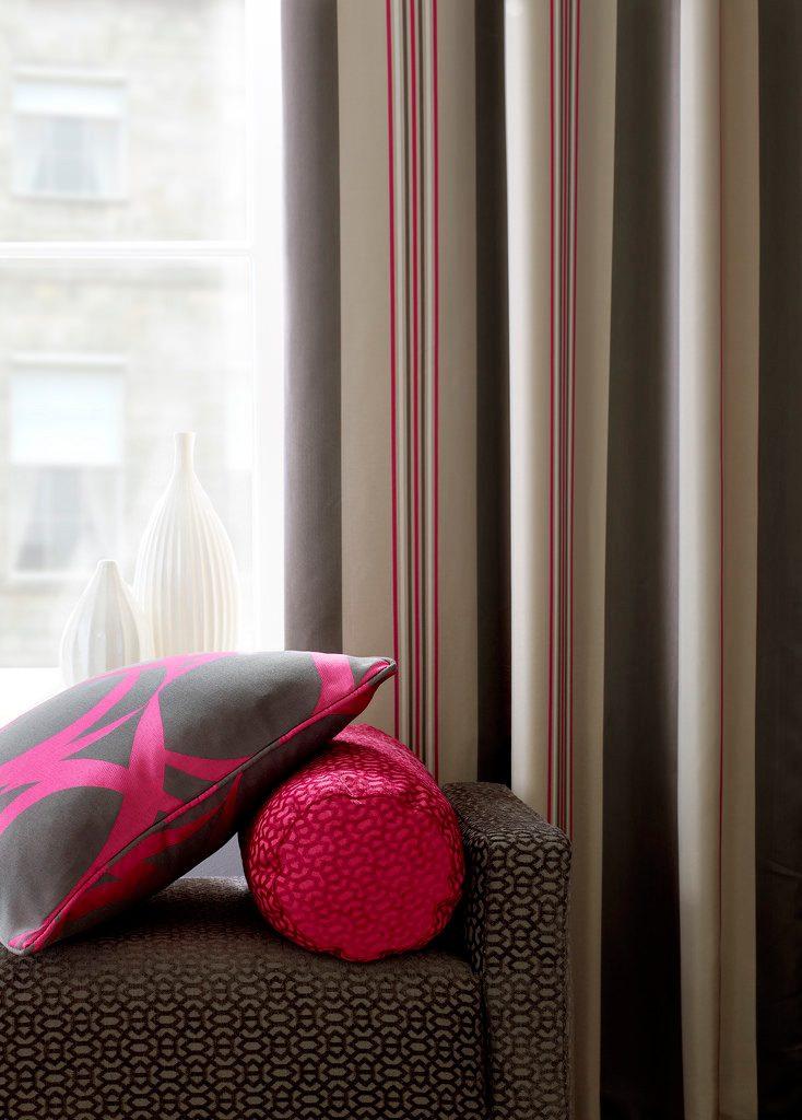coussin posé sur un canapé avec rideaux derrière et vue exterieur