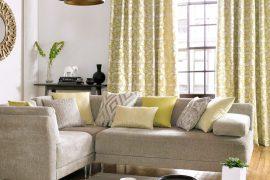 salon avec majorité couleur jaune. Table canapé avec fenêtre et rideaux motif